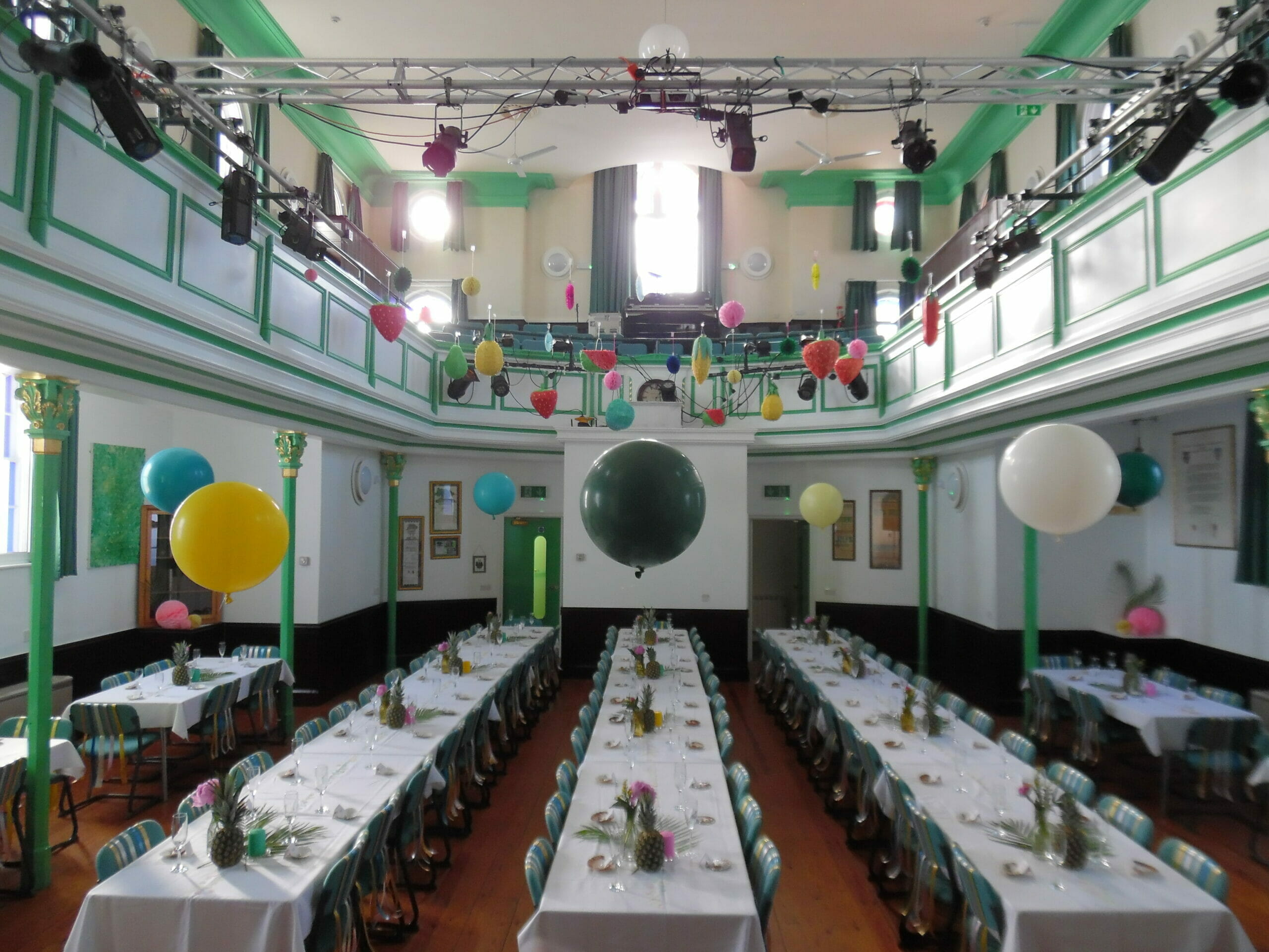 Photo shows a room layout with tressle tables and balloons